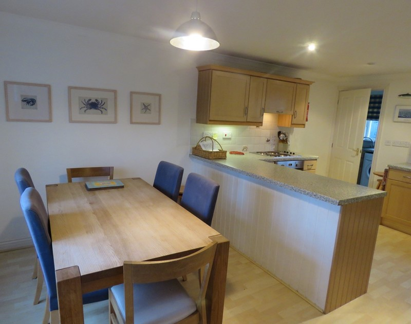 the comfortable dining room with seating for 6 in Marbeachow, a self catering holiday home in Tredrizzick near Rock, Cornwall.