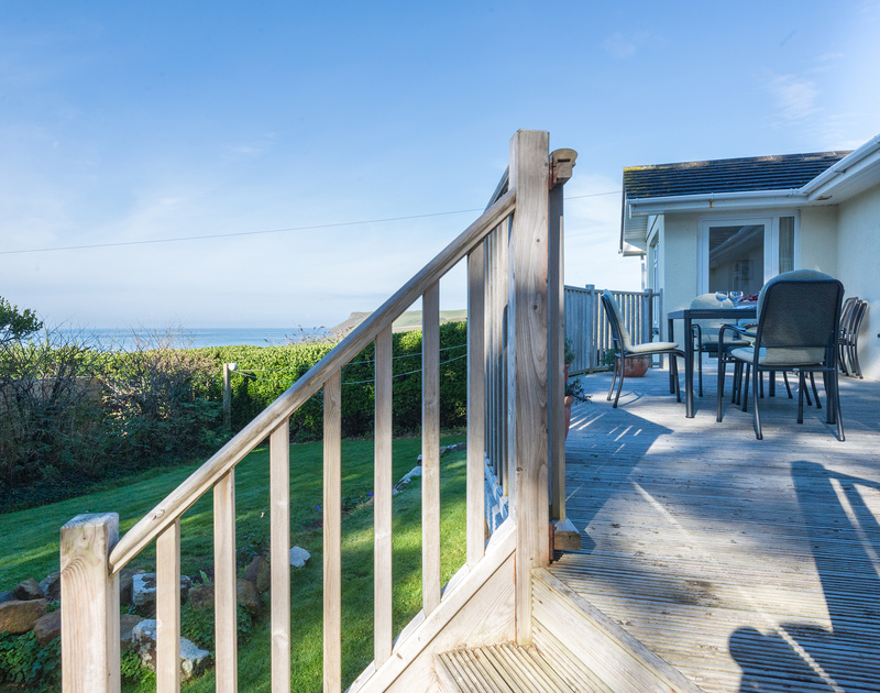 Dine alfresco on the raised decking whilst enjoying the views out to sea at The Glowdgie, a traditional self catering holiday home in New Polzeath, near Polzeath Cornwall.