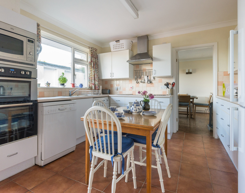 The well-equipped kitchen with a small breakfast dining table at The Glowdgie, a traditional self catering holiday home in New Polzeath, near Polzeath Cornwall.