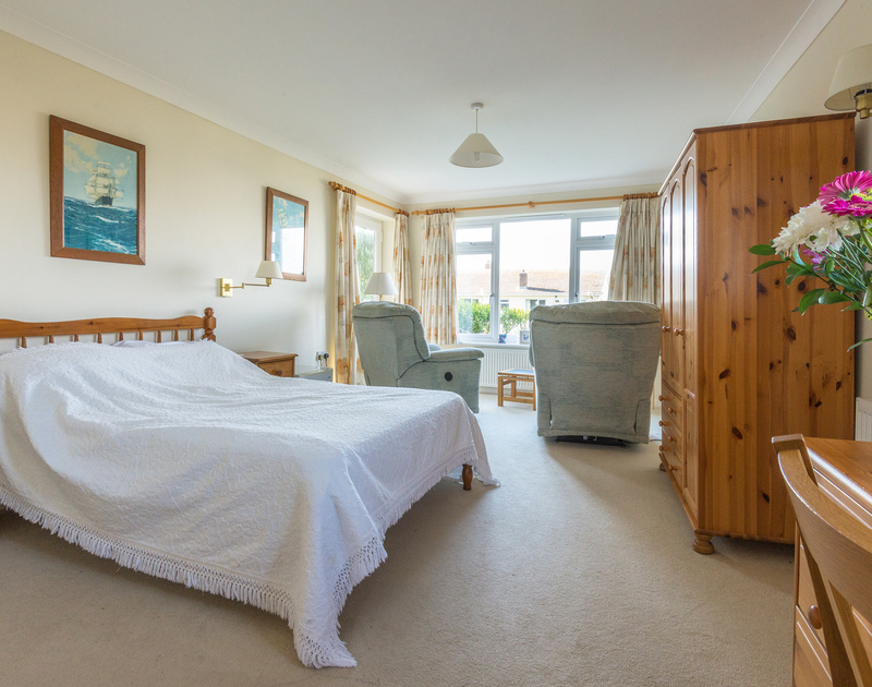 The spcious master bedroom with a double bed and ensuite bathroom with a separate shower in The Glowdgie, a traditional self catering holiday home in New Polzeath, near Polzeath Cornwall.