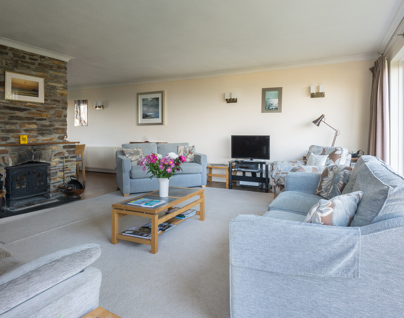 The cosy living room with a wood burner at The Glowdgie, a traditional self catering holiday home in New Polzeath, near Polzeath Cornwall.