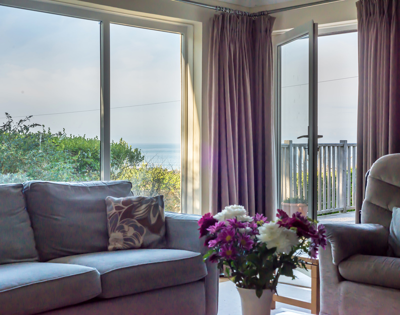 Gorgeous sea views and access out onto the decking from the living room at The Glowdgie, a traditional self catering holiday home in New Polzeath, near Polzeath Cornwall.