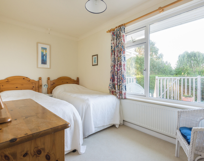 Twin bedroom with gorgeous sea views and a adjacent family bathroom in The Glowdgie, a traditional self catering holiday home in New Polzeath, near Polzeath Cornwall.