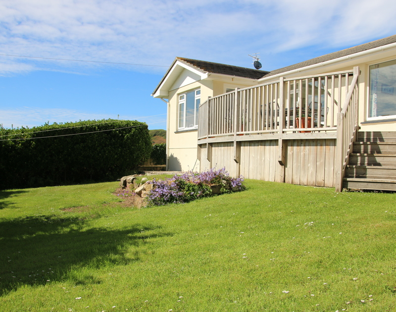 Private enclosed garden at The Glowdgie with gorgeous sea views from the decking, a traditional self catering holiday home in New Polzeath, near Polzeath Cornwall.
