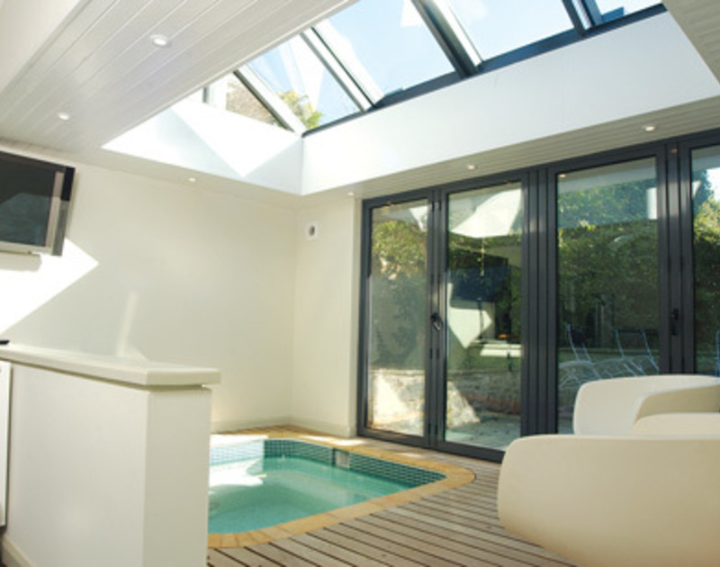 The indoor hot tub at Torquil, a gorgeous coastal country house at Daymer Bay, with bifold doors to the garden