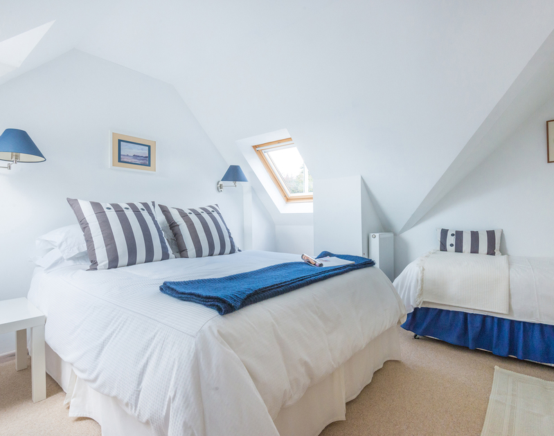 A crisp blue and white themed first floor double bedroom awaits at Sea Gulls in Porhtilly on the Camel Estuary in north Cornwall