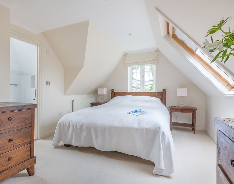 The ensuite master bedroom of Bodare 8, holiday rental at Daymer Bay, Cornwall, with kingsize bed and partially vaulted ceiling.