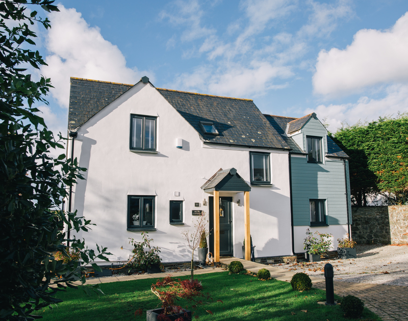 The picture perfect exterior of Myth Cottage in Rock, Cornwall - with a garage and lawned front garden