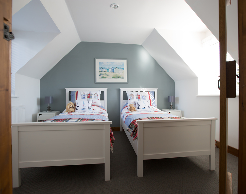 The ligth filled twin bedroom at Myth Cottage in Rock, Cornwall has two full size single beds