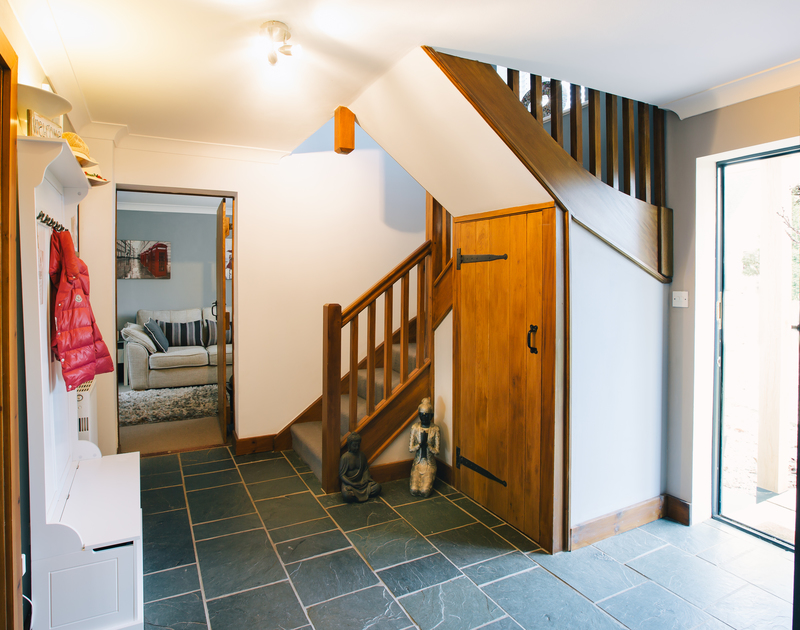 The welcoming entrance hall at Myth Cottage in Rock, Cornwall with its slate floor, WC and under stair storage