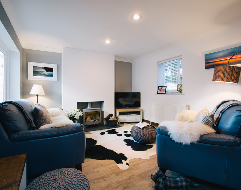 The stylish sitting room at Myth Cottage in Rock has been beautifully decorated with wood floors and a modern log burner