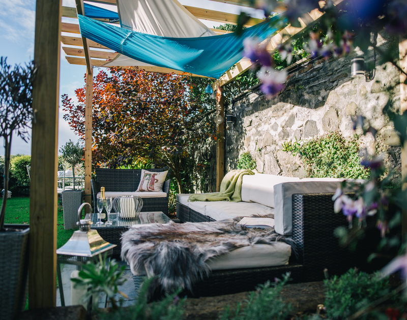 Relax with friends and family in the pretty seating area in the lawned garden at Myth Cottage in Rock, Cornwall