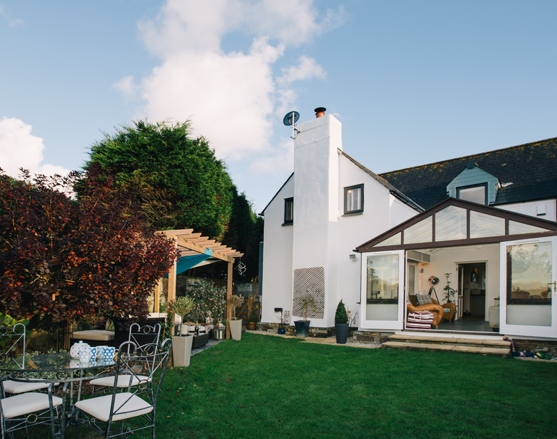 The lawned rear garden at Myth Cottage has mature shrubs and bedding plants, a patio table and chairs and pergola with a rattan corner sofa