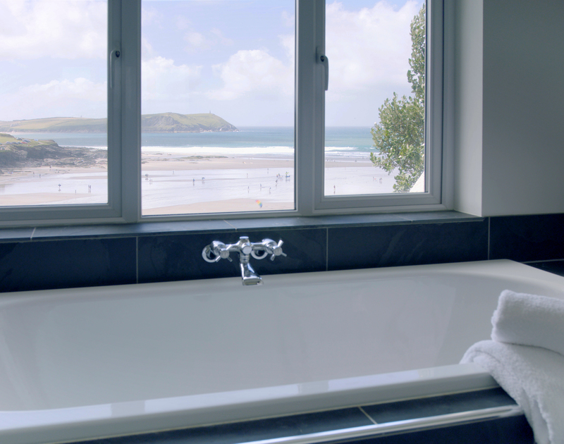 A beautiful bathroom with stunning sea views from the bath itself at Treverden, a self catering holiday rental in an unbeatable spot at New Polzeath, Cornwall.