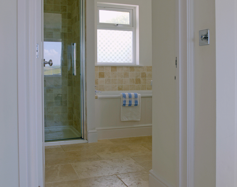 The second bedroom at Treverden in Polzeath has a balcony and an ensuite bathroom with separate shower.