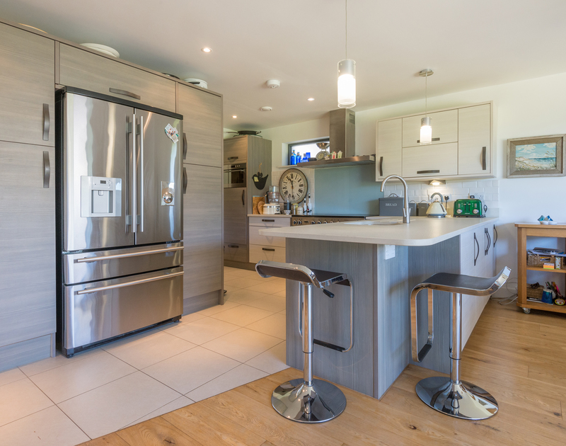 Enjoy sociable living in the luxury open plan kitchen at Borlase, a contemporary self-catering holiday house in Polzeath, Cornwall