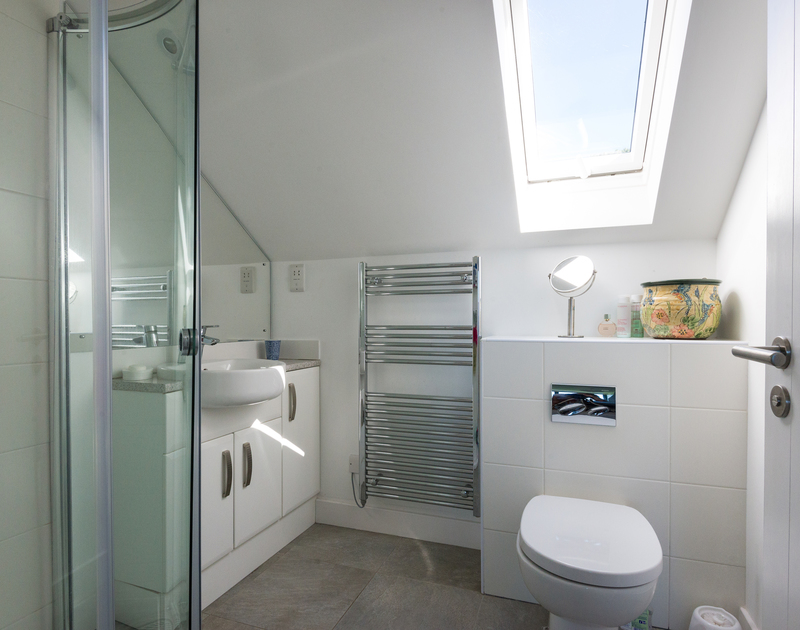 The sleek master bedroom at self catering holiday house Borlase in Polzeath, has an ensuite shower room