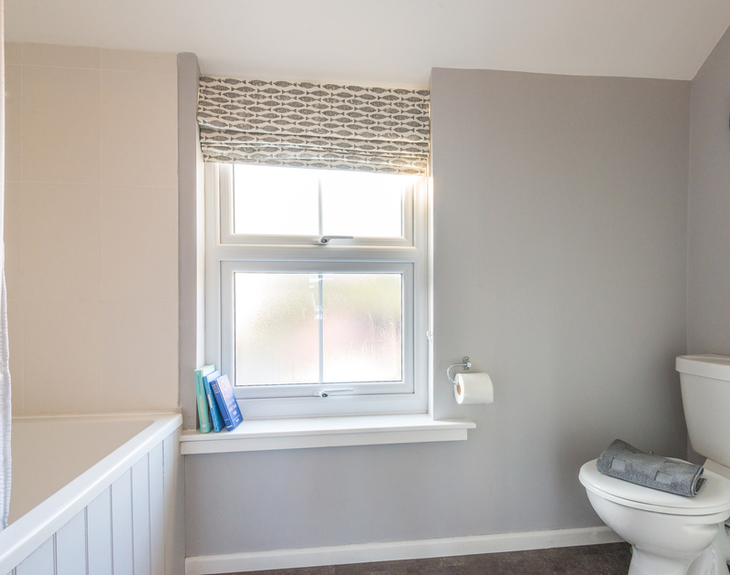 The family bathroom at The Porthole has a large window creating a light welcoming space at The Porthole in Port Isaac.
