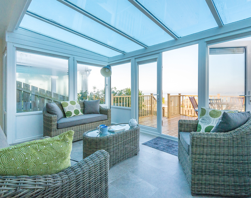 The spacious and light conservatory has sea and coastal views leading out onto a decked terrace at self catering holiday house The Porthole, Port Isaac.