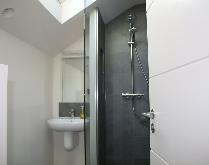 The sleek ensuite shower room for the king bedroom at self catering holiday house by the sea Mordros in North Cornwall.