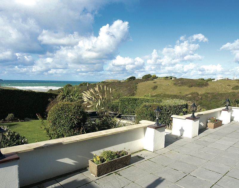 The sunny terrace, pretty garden and stunning sea views from Sunset, a self catering holiday house in Polzeath, North Cornwall.