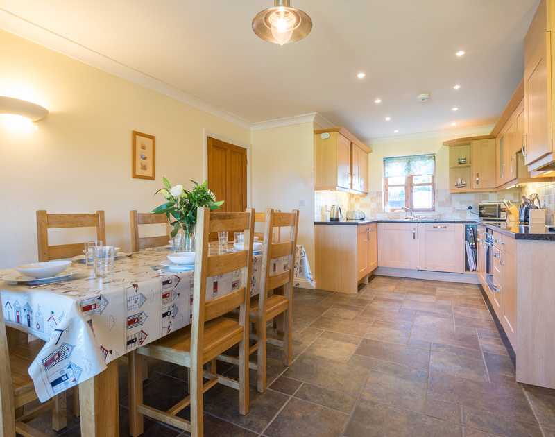The cosy, light dining area in Puffin Cottage, a holiday cottage in Rock, Cornwall.