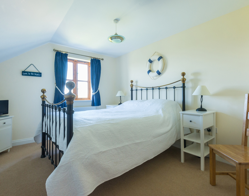 The nautical king size bedroom in Puffin Cottage, a self catering holiday house to rent in Rock in North Cornwall.