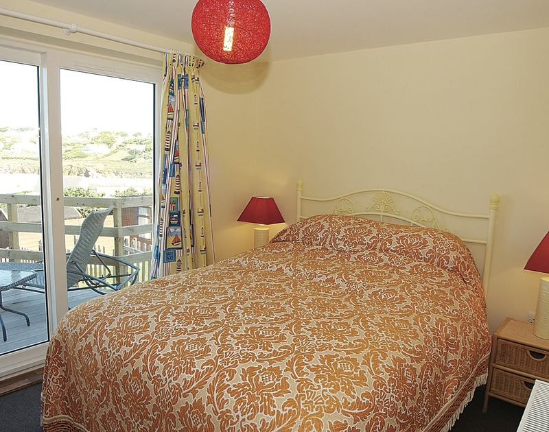 The double bedroom of Malindi, a holiday house at Polzeath, with its kingsize bed and sea views through french windows.