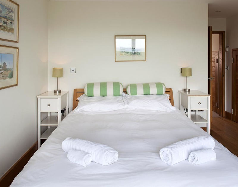 Comfortable and uncluttered, the lower ground floor double bedroom at Ossco has an adjacent bathroom
