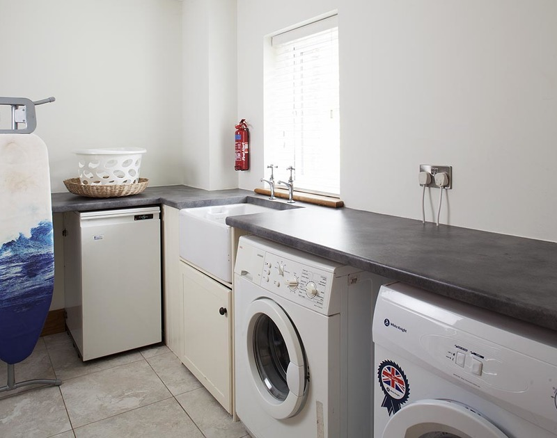 A spacious utility room at Ossco in Polzeath is perfect for storing wetsuits and beach gear
