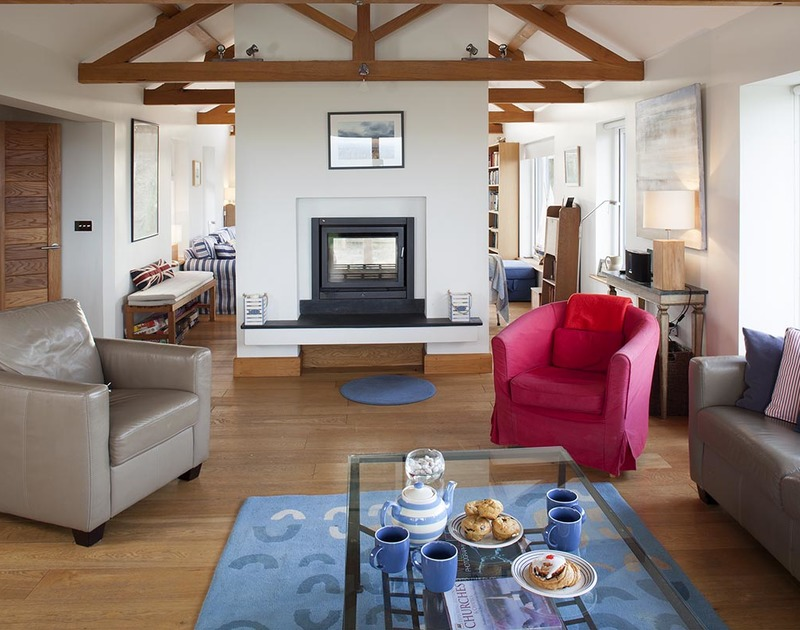 The spacious living room at Ossco in Polzeath offers two separate spaces, divided by a large modern woodburner