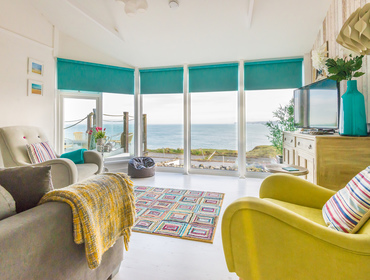 The stylish sitting room with breathtaking views of the coast, a contemporary self catering holiday home in Port Isaac, Cornwall