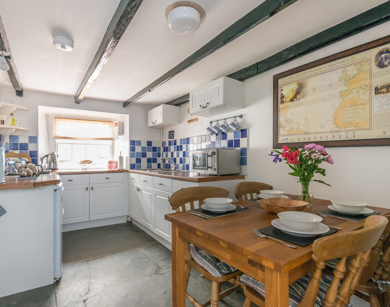 Open plan kitchen-diner of Cloam Cottage, with characterful flagstone flooring and beamed ceiling