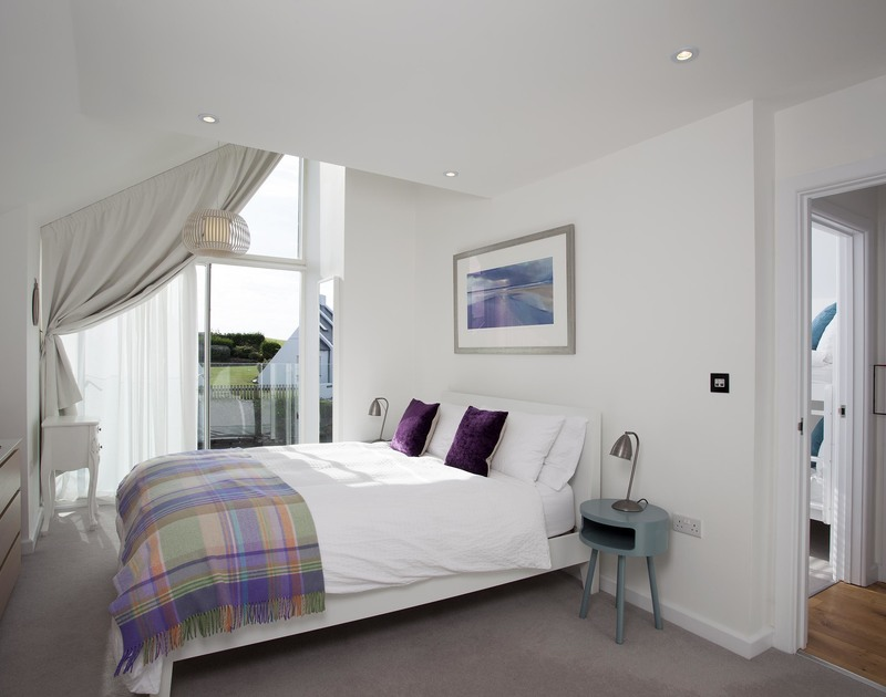 The master bedroom at 3 The Sands in Polzeath has a glass Juliet balcony and ensuite shower room.