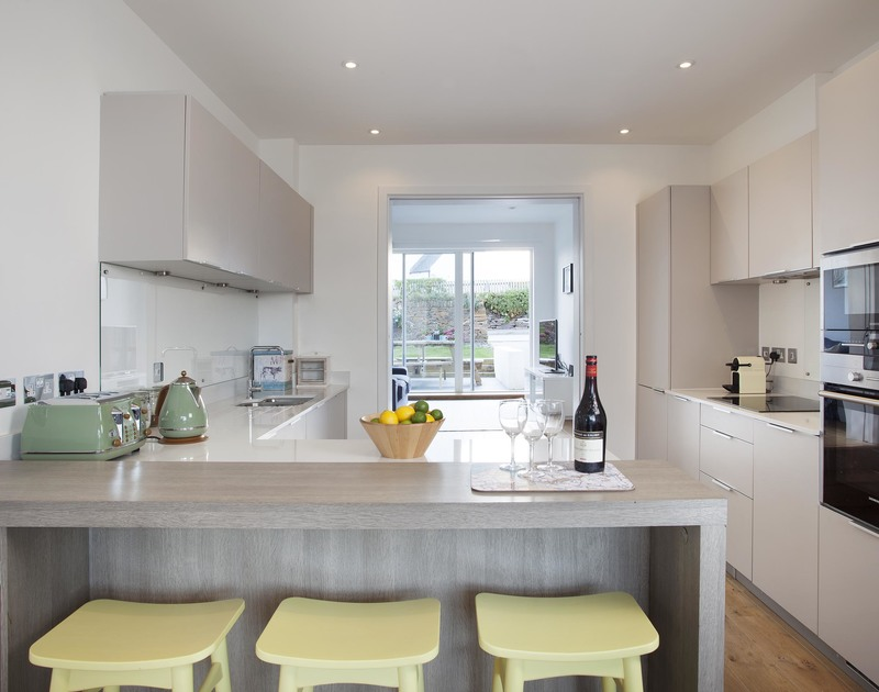 The sleek, contemporary kitchen and breakfast bar in 3, The Sands, a luxury holiday house in Polzeath on the North Cornish Coast.