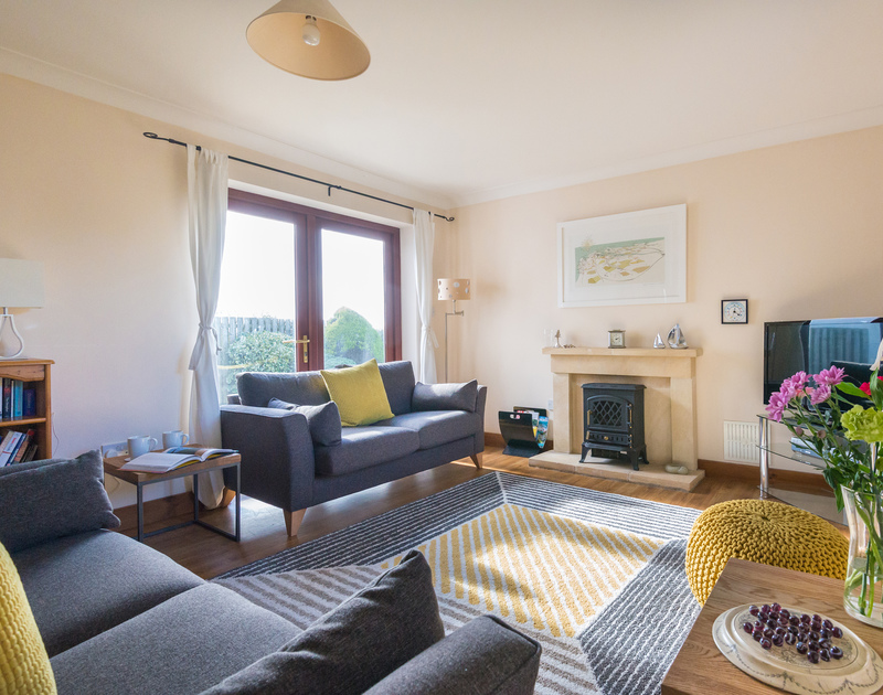 Relax infront of the woodburner and TV in Dolphin Cottage's sitting room, with its grey and yellow furnishings