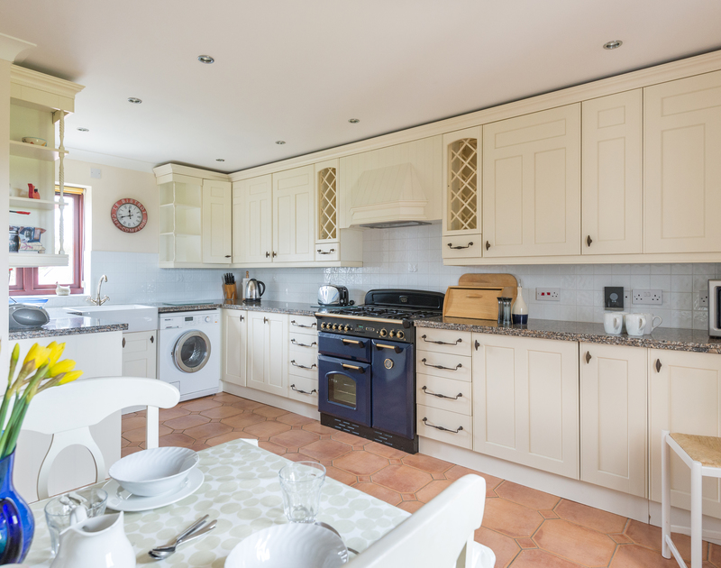 The classic kitchen of Dolphin Cottage, a holiday house in Rock, Cornwall, with modern range cooker and butler sink.