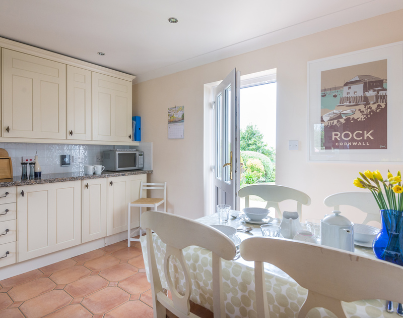 Step out into the private garden from the kitchen at Dolphin Cottage, a traditional self catering cottage in Rock, Cornwall.