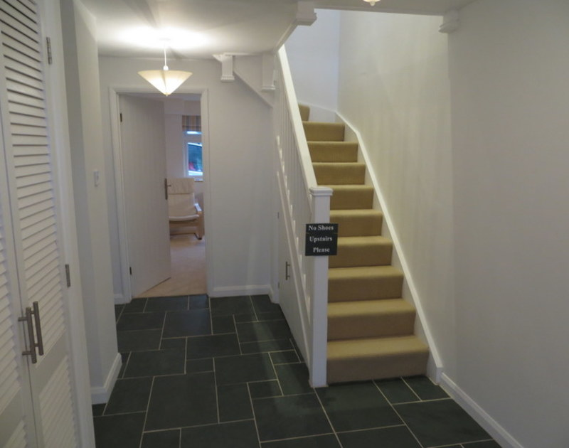 Slate tiled entrance hall at Slipway 21, a holiday rental in Rock, with stairs leading to the first floor