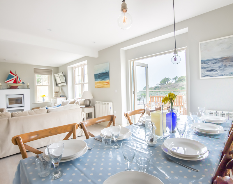 The dining area, part of the social living space with access out onto the terrace in Westray House, a stylishly refurbished holiday house to rent in Polzeath, North Cornwall.