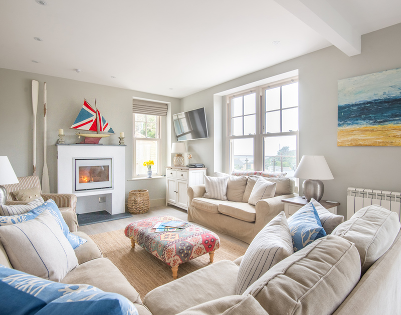 The comfortable sitting room with modern wood burner in Westray House, a self catering holiday house to rent in Polzeath, North Cornwall.