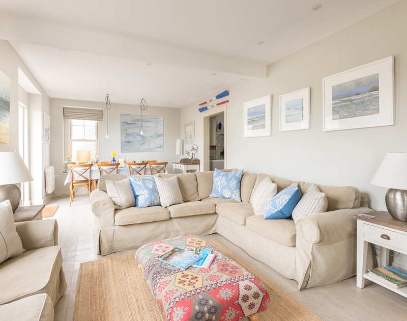 The dining and sitting area in Westray House with access out onto the decked terrace where you can hear the waves and soak up the sun at Westray House, a self catering holiday cottage in Polzeath, North Cornwall.