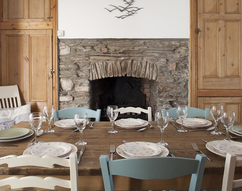 Dine with family and friends by the Cornish stone open fire feature at Fronthill House, a traditional self catering holiday cottage in Port isaac, Cornwall