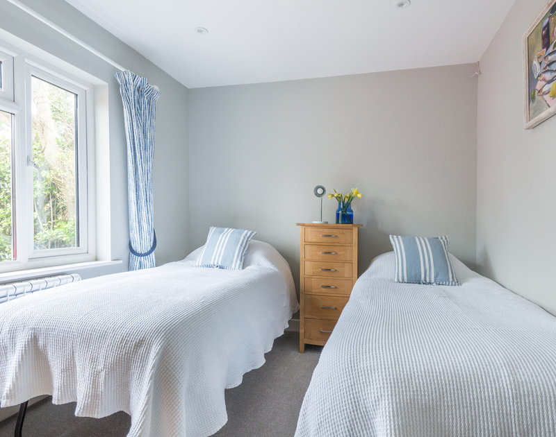 Scarthoe's stylish ground floor twin bedroom, with blue and white stripy soft furnishings