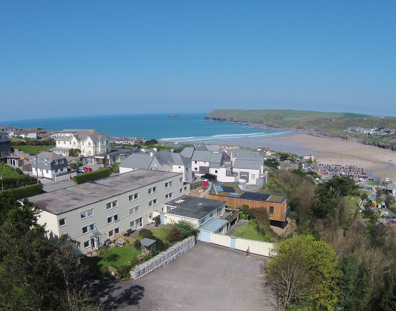 The aerail exterior of Westward 7 in relation to the surfing beach and sea, a self-catering holiday apartment in Polzeath, Cornwall