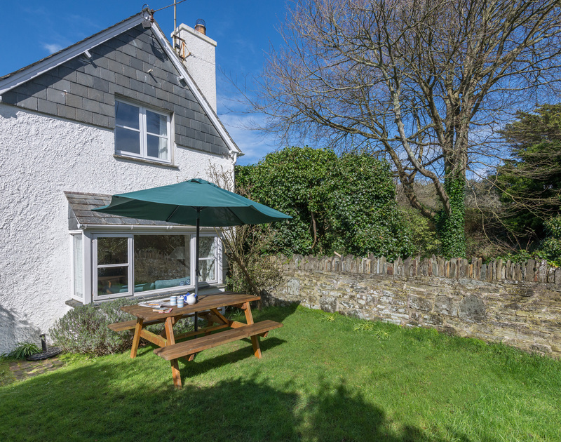 The exterior view and garden of Little Torquil, a characterful self-catering holiday cottage at Daymer Bay, Cornwall