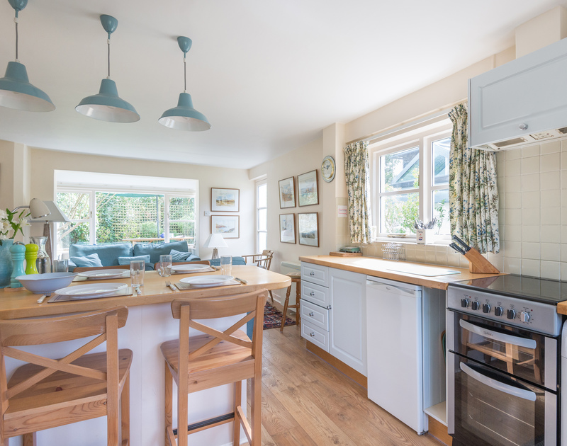 The contemporary open plan kitchen, dining and living area in Little Torquil, a traditional holiday cottage in Daymer Bay, Cornwall.
