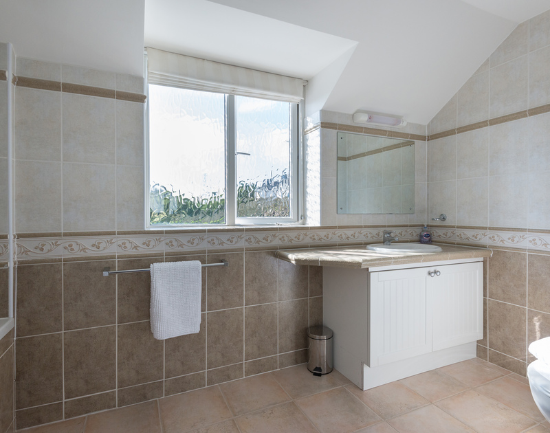Attractive floor and wall tiles in the master bedroom's ensuite bathroom