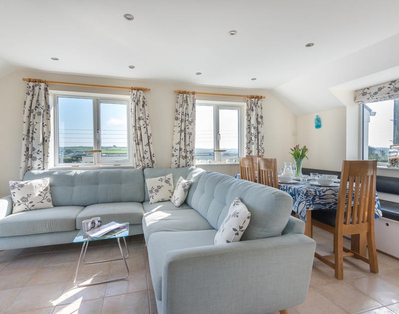 Throw open the doors to let the sea air in and relax and watch a classic movie in the spacious living area at Polmorla in Polzeath, Cornwall