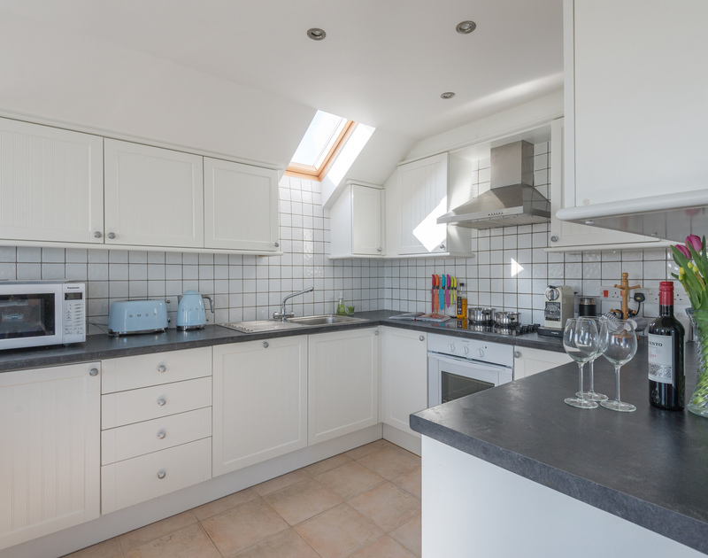 The contemporary kitchen as part of the open plan social room on the first floor at Polmorla, a self catering holiday cottage in Polzeath, Cornwall